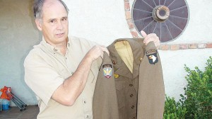 Dan Potter holds his father's uniform jacket. (Photo Contributed)